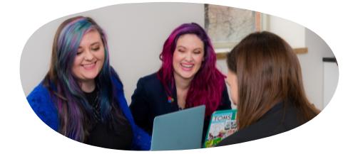 Group of three women sitting down around a laptop.