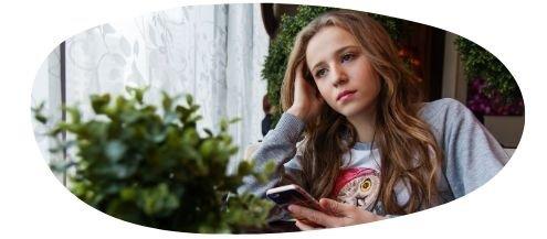 Girl on phone looking thoughtful
