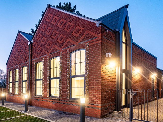 Great Kimble Church of England School: a medium sized building with pattern brickwork and exterior lighting