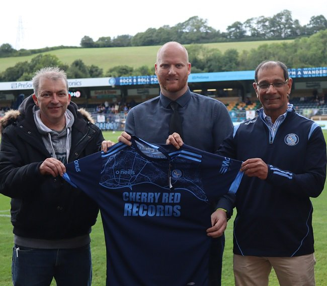 Des Mackin (Buckinghamshire Foster Carer), Mark Fawkes (Head of Fundraising and Communications, Wycombe Wanderers) and Cllr Arif Hussain (Chairman of the High Wycombe Community Board and Deputy Cabinet Member for Communities) holding a football shirt at Wycombe Wanderers.