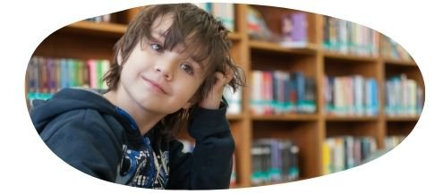 Young boy in a library with hand rested against his head
